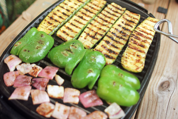 Grilling sliced zucchini, green bell pepper, and red onion