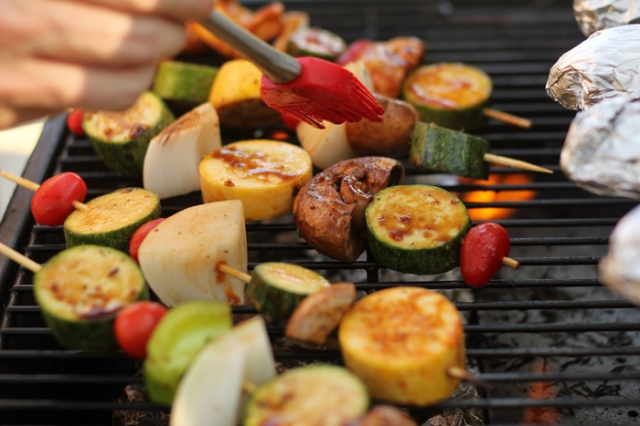 Karl marinates vegetable skewers on the grill